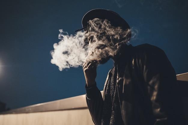 Porträt des jungen schwarzen mannes, der rauchende zigarette im freien steht