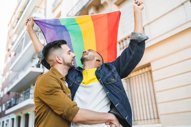 Porträt des jungen schwulen paares, das ihre liebe mit regenbogenfahne auf der straße umarmt und zeigt. lgbt und liebeskonzept.
