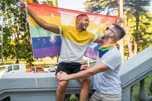 Porträt des jungen schwulen paares, das ihre liebe mit regenbogenfahne in der straße umarmt und zeigt. lgbt und liebeskonzept.