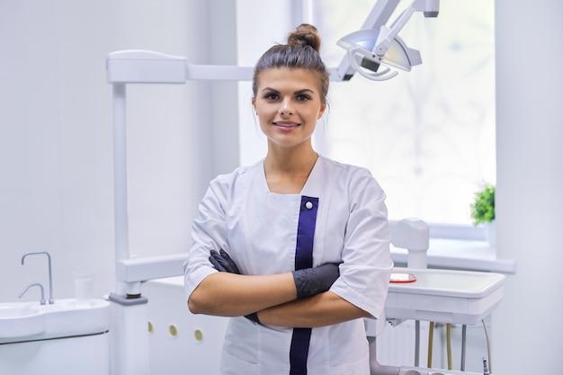 Porträt des jungen selbstbewussten lächelnden zahnarztes in der zahnarztpraxis