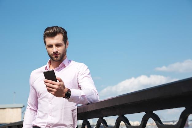 Porträt des jungen selbstbewussten mannes, der smartphone nahe fluss verwendet