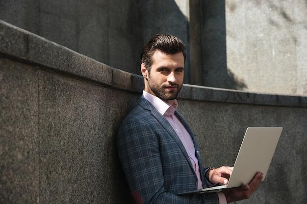 Porträt des jungen selbstbewussten mannes im anzug unter verwendung des laptops