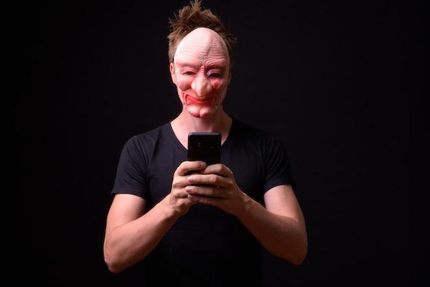 Porträt des jungen skandinavischen mannes, der maske auf schwarz trägt