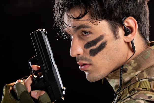 Porträt des jungen soldaten in tarnung, der mit der waffe auf die schwarze wand zielt
