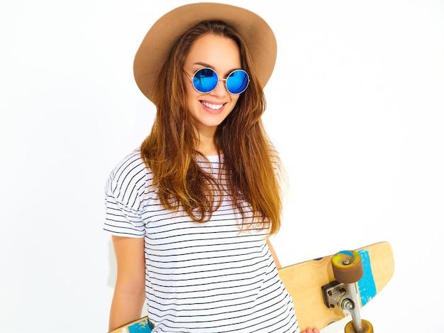 Porträt des jungen stilvollen frauenmodells im zufälligen sommer kleidet im braunen hut, der mit longboard schreibtisch aufwirft. isoliert auf weiss
