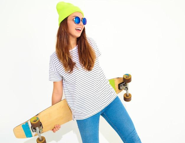 Porträt des jungen stilvollen frauenmodells im zufälligen sommer kleidet im gelben beaniehut, der mit longboard schreibtisch aufwirft. isoliert auf weiss