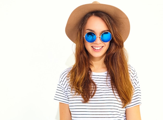 Porträt des jungen stilvollen lachenden frauenmodells im zufälligen sommer kleidet im braunen hut, der auf weißer wand lokalisiert wird