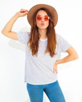Porträt des jungen stilvollen lachenden frauenmodells im zufälligen sommer kleidet im braunen hut mit dem natürlichen make-up, das auf weißer wand lokalisiert wird. luft küssen