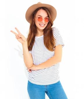 Porträt des jungen stilvollen lachenden frauenmodells im zufälligen sommer kleidet im braunen hut mit dem natürlichen make-up, das auf weißer wand lokalisiert wird. zeige friedenszeichen