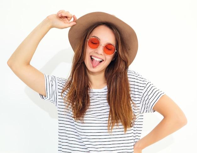 Porträt des jungen stilvollen lachenden frauenmodells im zufälligen sommer kleidet im braunen hut mit dem natürlichen make-up, das auf weißer wand lokalisiert wird. zeigt ihre zunge