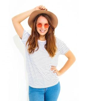 Porträt des jungen stilvollen lachenden frauenmodells im zufälligen sommer kleidet im braunen hut mit dem natürlichen make-up, das auf weißer wand lokalisiert wird. zwinker