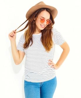 Porträt des jungen stilvollen lachenden frauenmodells im zufälligen sommer kleidet im braunen hut mit dem natürlichen make-up, das auf weißer wand lokalisiert wird.