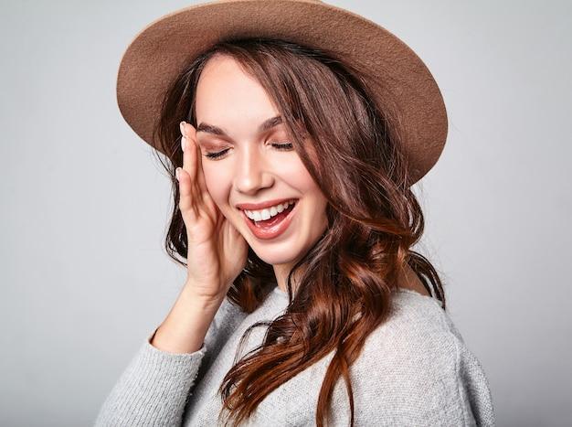 Porträt des jungen stilvollen lachenden modells in der grauen lässigen sommerkleidung im braunen hut mit natürlichem make-up