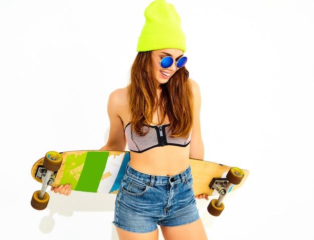 Porträt des jungen stilvollen lächelnden frauenmodells in der zufälligen sommerbadebekleidungskleidung und in der gelben mütze, die mit longboard schreibtisch aufwerfen. isoliert auf weiss