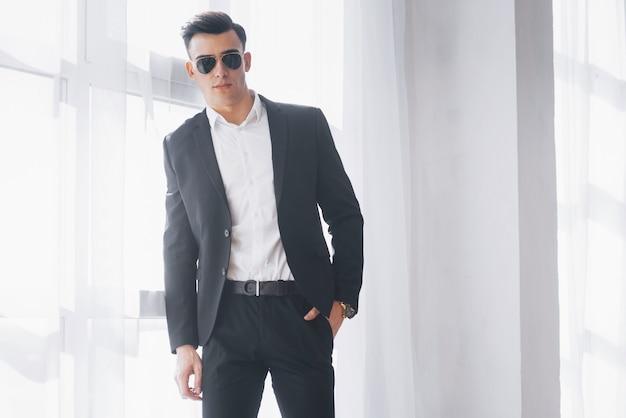 Porträt des jungen stilvollen mannes in der klassischen geschäftskleidung, die im weißen raum steht.