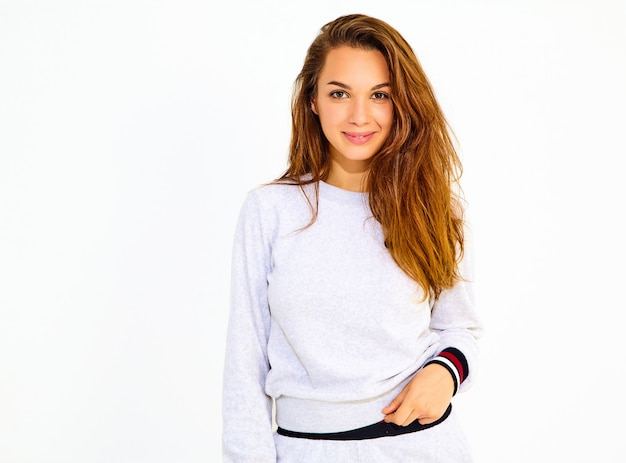 Porträt des jungen stilvollen netten frauenmodells im zufälligen grauen sportkostüm mit dem natürlichen make-up lokalisiert auf weißer wand