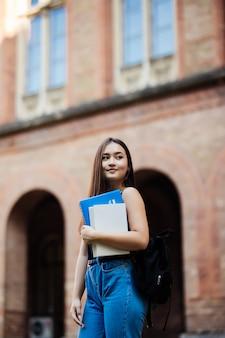 Porträt des jungen studenten, der buch am campus im freien hält