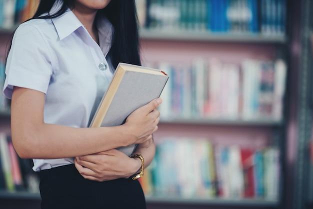 Porträt des jungen studenten ein buch in einer bibliothek lesend