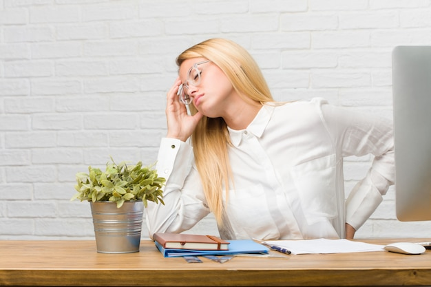 Porträt des jungen studenten sitzend auf ihrem schreibtisch, der aufgaben mit rückenschmerzen wegen des arbeitsstresses erledigt