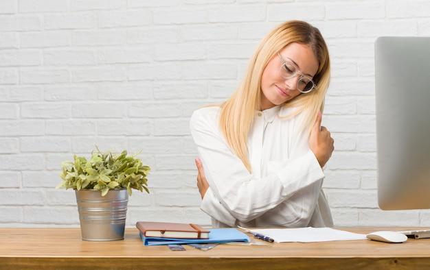 Porträt des jungen studenten sitzend auf ihrem schreibtisch, der aufgaben stolz und überzeugt, zeigend finger, beispiel zum folgen, konzept der zufriedenheit, arroganz und gesundheit