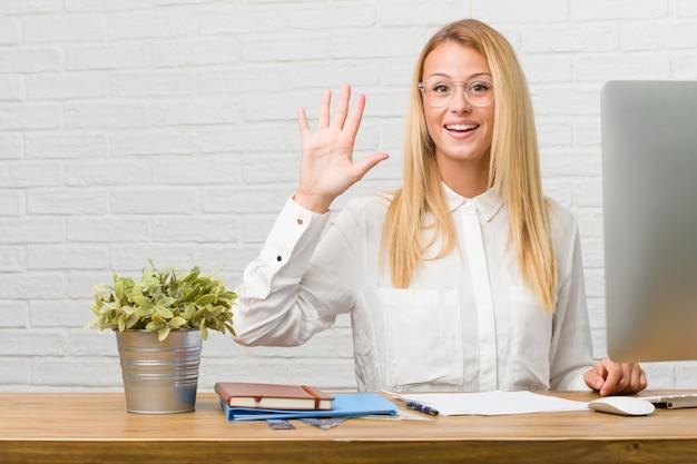 Porträt des jungen studenten sitzend auf ihrem schreibtisch, der die aufgaben zeigt nr. fünf, symbol von c tut