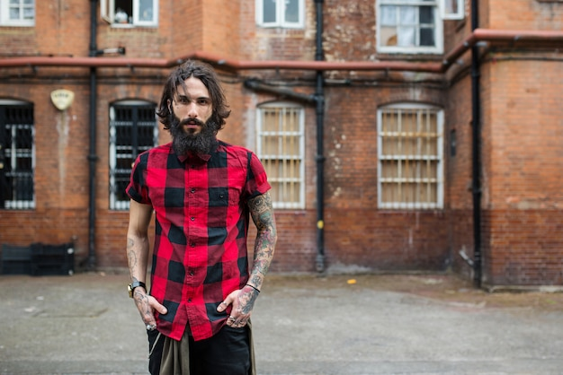 Porträt des jungen tätowierten mannes, der in shoreditch-stadt steht. london, vereinigtes königreich. hipster-stil.