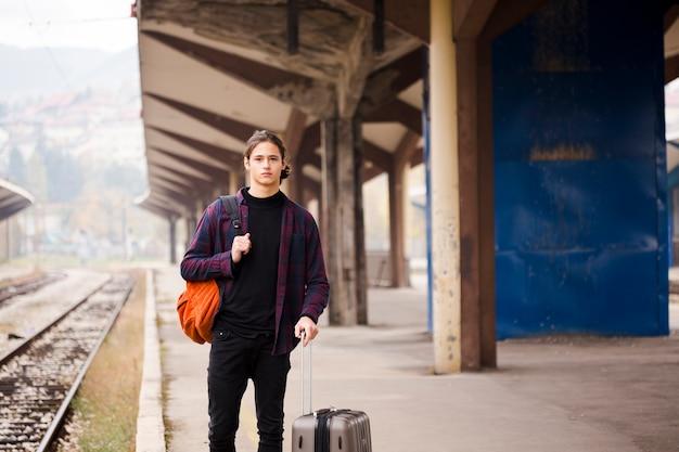 Porträt des jungen touristen auf einen zug wartend