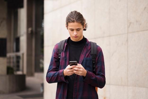 Porträt des jungen touristen sein telefon überprüfend