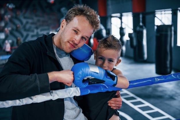Porträt des jungen trainers mit dem kleinen jungen, der im boxring steht.