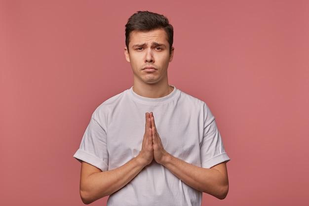 Porträt des jungen traurigen kerls im leeren t-shirt, hofft auf glück und zeigt gebetsgeste, steht auf rosa mit unglücklichem ausdruck.