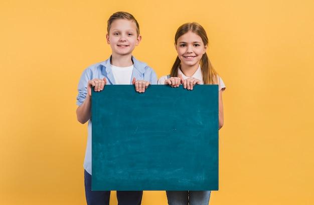 Porträt des jungen und des mädchens, die die grüne tafel steht gegen gelben hintergrund hält