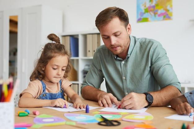 Porträt des jungen vaters, der mit kleiner tochter zeichnet, während kindergartenklasse zusammen genießt