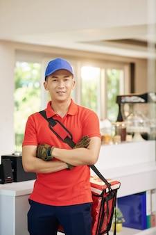 Porträt des jungen vietnamesischen kuriers, der im café mit tragbarer kühltasche steht