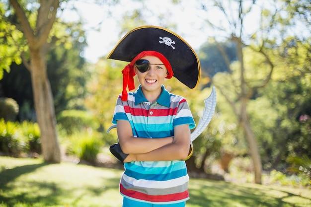 Porträt des jungen vortäuschend, ein pirat im park zu sein