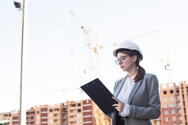 Porträt des jungen weiblichen architekten, der an klemmbrett am architekturprojekt arbeitet