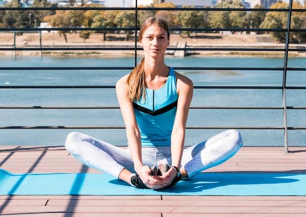 Porträt des jungen weiblichen athleten, der ihr bein sitzt auf übungsmatte an draußen ausdehnt