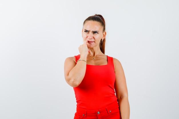 Porträt des jungen weiblichen beißenden nagels im roten trägershirt, in der hose und in der nachdenklichen vorderansicht