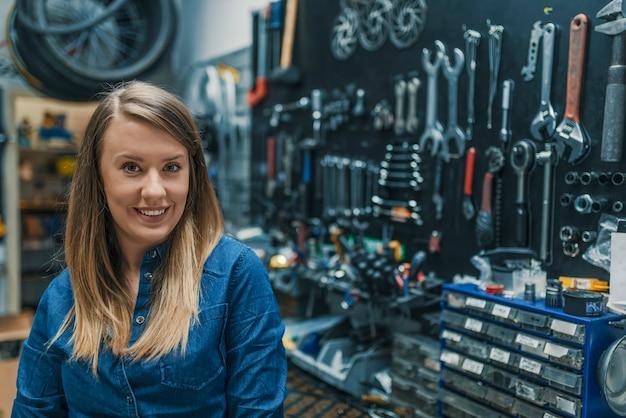 Porträt des jungen weiblichen mechanikers im fahrradladen