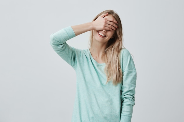 Porträt des jungen weiblichen modells, das ihre augen hinter der handfläche versteckt und breit lächelt, während es freude fühlt.