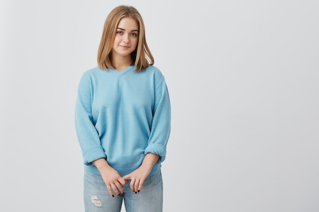 Porträt des jungen zarten blonden europäischen mädchens mit gesunder haut, die blaues oberteil und jeans trägt, die mit ruhigem oder angenehmem ausdruck schauen. kaukasisches frauenmodell mit blondem haar, das drinnen aufwirft