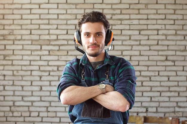 Porträt des jungen zimmermanns, der seine arme kreuzt und kamera betrachtet