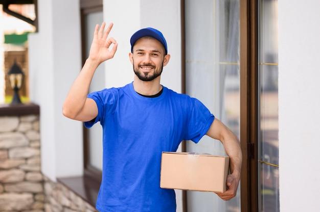 Porträt des jungen zustellers, der paket trägt