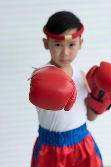 Porträt des jungenboxers in den roten boxhandschuhen