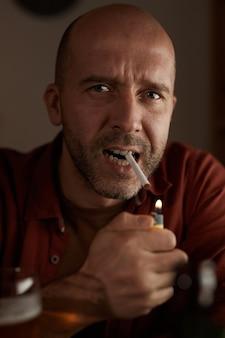 Porträt des kahlen reifen mannes, der die zigarette am tisch raucht
