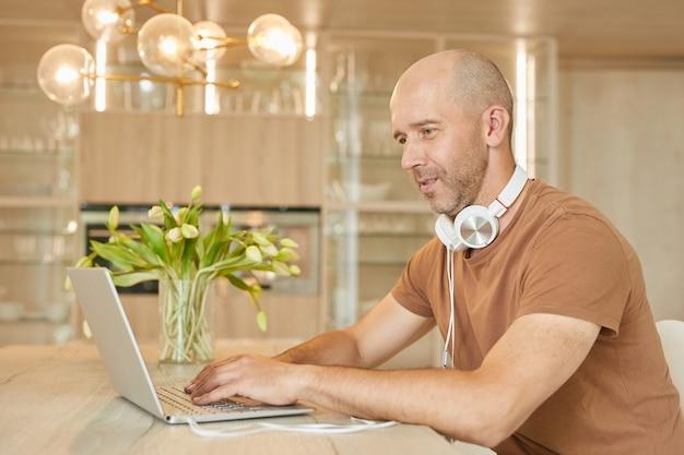 Porträt des kahlen reifen mannes, der laptop verwendet, während von zu hause aus arbeitend und musik hörend