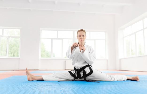 Porträt des karatemädchenschwarzgurtgrades, ihre beine vor hartem training ausdehnend.