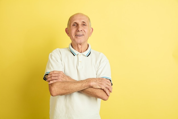 Porträt des kaukasischen älteren mannes lokalisiert auf gelbem studio