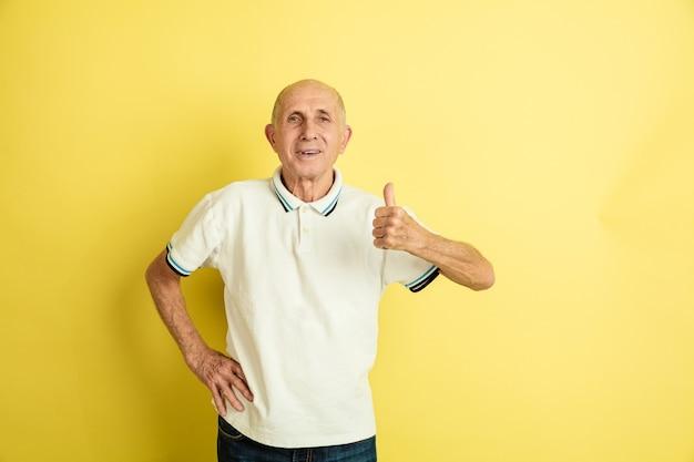 Porträt des kaukasischen älteren mannes lokalisiert auf gelbem studiohintergrund