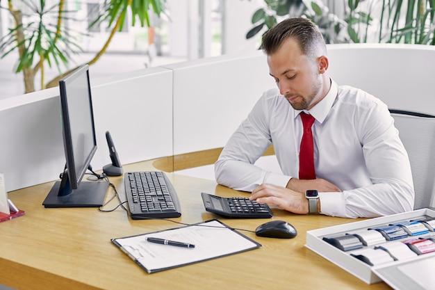 Porträt des kaukasischen ernsthaften managers unter verwendung des taschenrechners