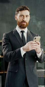 Porträt des kaukasischen freudigen geschäftsmannes im büro sms auf dem smartphone.